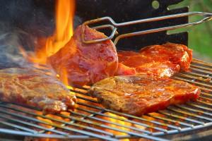 Fleisch auf dem Grill wird mit einer Grillzange gewendet
